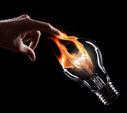 Light bulb with fire. On black background Royalty Free Stock Photography