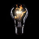 Light bulb with fire. On black background Royalty Free Stock Images