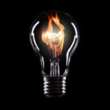 Light bulb with fire. On black background Stock Photography