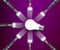 Light bulb between forks Royalty Free Stock Photo