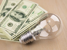 Light bulb in front of dollar bill stack Royalty Free Stock Photos