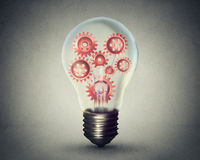 Light bulb with gears and cogs working together Royalty Free Stock Image