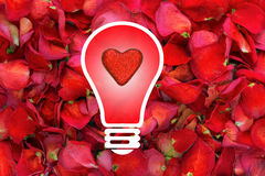 Light bulb with glitter heart in centre on dried rose petal background royalty free stock photo