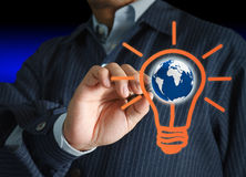 Light bulb and globe. Hand with a pen drawing light bulb and globe Royalty Free Stock Photo