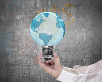 Light bulb of globe shape with man's hand holding Stock Photo