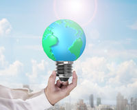 Light bulb of globe shape with man's hand holding Royalty Free Stock Photography