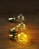 Light bulb glowing on a wooden background Royalty Free Stock Images
