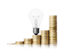 Light bulb on gold coins and graph them Royalty Free Stock Photos