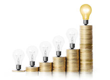 Light bulb on gold coins and graph them Stock Images