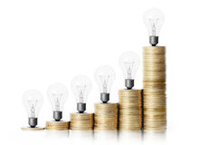 Light bulb on gold coins and graph them Royalty Free Stock Photo