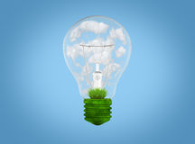 Light bulb with grass and clouds inside it. Stock Photos