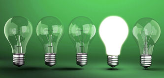 Light bulb on green background Royalty Free Stock Images