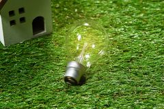 Light bulb on green natural background , green energy concept Stock Photos