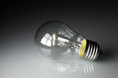 Light bulb on grey background Royalty Free Stock Photography
