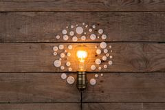 Retro light bulb and group of gears on wooden background - idea, innovation, teamwork and leadership concept. Space for text