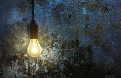Light bulb on grunge wall Stock Photography