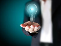 Light bulb in hand Stock Images