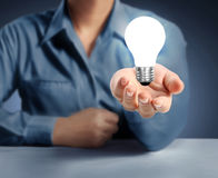 Light bulb on a hand Stock Photos