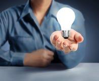 Light bulb on a hand Stock Photos