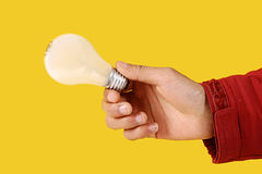Light bulb in hand. White light bulb in hand, isolated on Yellow Royalty Free Stock Photography