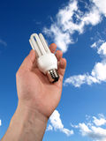 Light bulb in the hand. On sky background Stock Photography