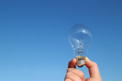 Light bulb and the hand in the blue sky Stock Images