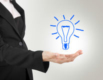 Light bulb in hand business woman. Royalty Free Stock Images
