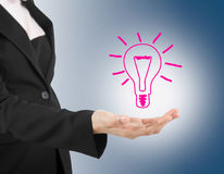 Light bulb in hand business woman on blue background. Stock Photos