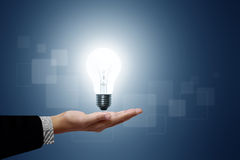Light bulb in hand businessman. On blue background stock photo