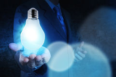 Light bulb in hand businessman on blue tone Stock Images