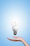 Light bulb in hand with gray background. Royalty Free Stock Image
