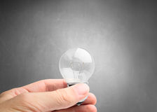 Light bulb in hand on gray background Stock Images