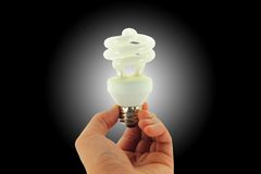 Light Bulb In Hand Isolated On Black And Spotlight stock images