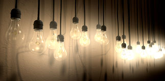 Light Bulb Hanging Wall Arrangement Perspective. A front view row of displayed illuminated hanging lightbulbs casting various shadows on a brown wall background royalty free stock images