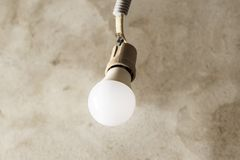 . light bulb hanging on the wires. wall background of concrete. new construction concept. Light bulb hanging on the wires. wall background of concrete. new royalty free stock images