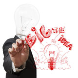 Light bulb head draws the big idea with red pen Stock Photography
