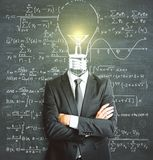 Solution concept. Light bulb headed businessman with folded arms standing on chalkboard wall background with mathematical formulas. Solution concept Stock Photography