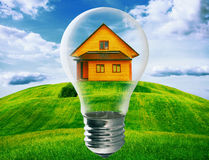 Light bulb with house inside royalty free stock photos