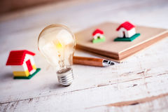 Light bulb and house model Stock Images