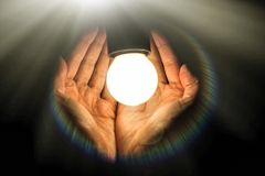 Light bulb in humans hands on black background, energy saving an. D innovation concept stock image