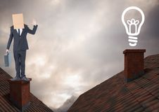 Light bulb icon and Businessman standing on Roofs with chimney and cardboard box on his head and dra. Digital composite of Light bulb icon and Businessman Stock Photo