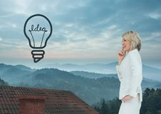 Light bulb icon and Businesswoman standing on Roof with chimney and misty landscape Royalty Free Stock Photo