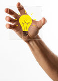 Light bulb icon on glass in hand. Bright yellow light bulb icon on piece of square shaped glass held in a single hand over isolated white background Stock Image