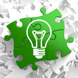 Light Bulb Icon on Green Puzzle. Stock Photos