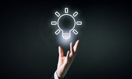 Light bulb icon. Hand of businessman holding drawn light bulb icon Stock Photography