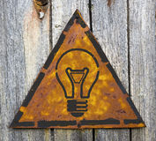 Light Bulb Icon on Rusty Warning Sign. Stock Photos