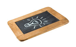 Light bulb icon. White chalk handwriting on isolated vintage slate blackboard Royalty Free Stock Images