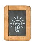 Light bulb icon. White chalk handwriting on isolated vintage slate blackboard Royalty Free Stock Image