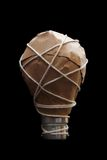 Light Bulb Idea Wrapped. Image of a light bulb wrapped in brown paper and string on black, conceptual ideas royalty free stock images