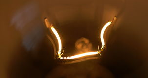 Light bulb isolated filament glow slow flashing. Light bulb isolated filament glow slow warm light flashing on black background 4k stock video